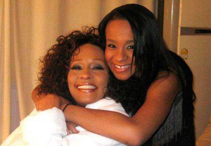 Whitney Houston (izq.) falleció un 11 de febrero, hace 3 años. Hoy, su hija, Bobbi Kristina Brown, quien la acompaña en la foto, permanece en estado de coma, y según informes de la familia, será desconectada hoy. (Archivo/excelsior.com.mx)