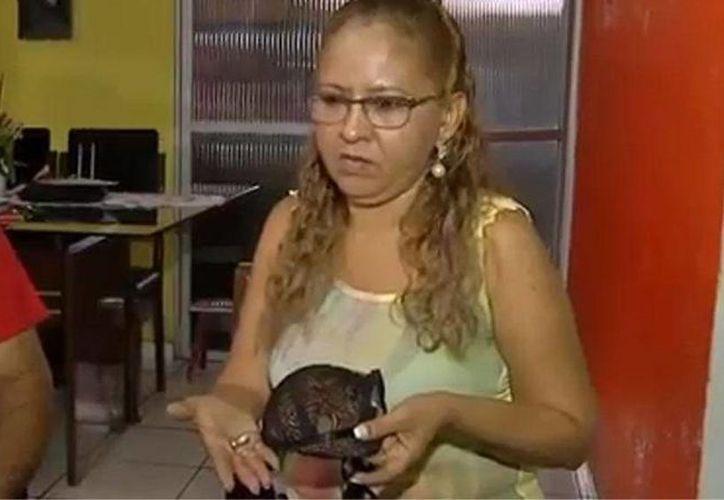 Ivete Medeiros muestra el sostén que literalmente le salvó la vida; la bala cayó en su seno izquierdo. (O Globo)