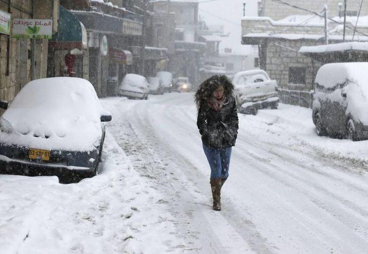 Una mujer camina bajo la nieve en una calle de la localidad de Majdal Shams, en el territorio israelí de los Altos del Golán. (EFE)
