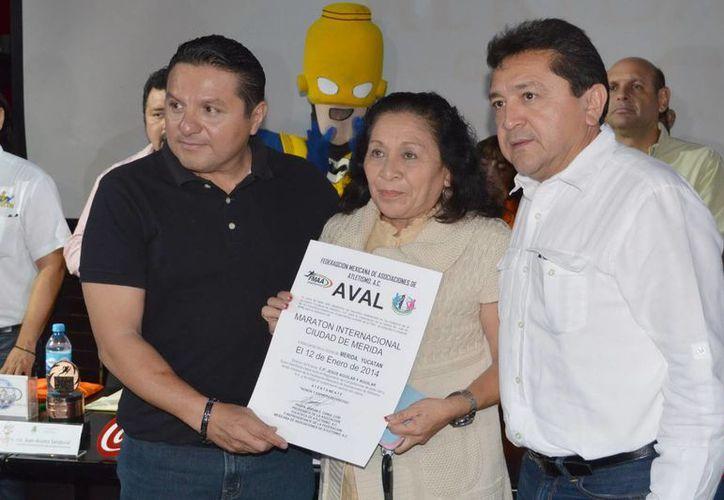 Jesús Aguilar, director del IMD; Míriam Canul, presidenta de la AYA, y el regidor Felipe Duarte, muestran el aval para el Maratón. (Milenio Novedades)