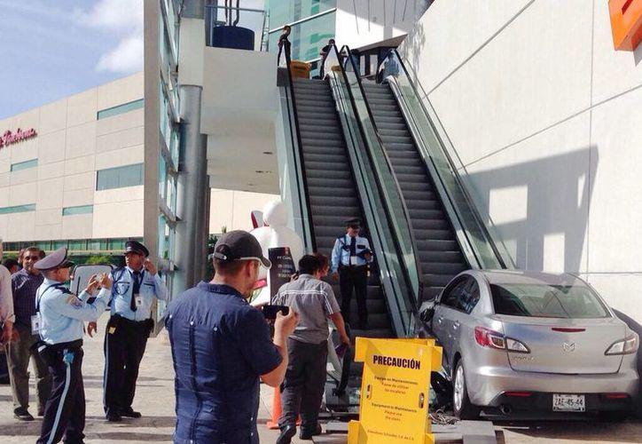 La conductora de un vehículo prácticamente se subió a las escalares eléctricas exteriores, en Plaza Altabrisa. (Aldo Pallota/SIPSE)