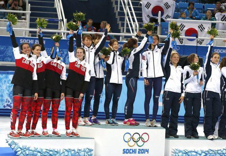 Las integrantes del equipo sur coreano (c) celebran hoy su medalla de oro en los relevos 3,000 metros en pista corta de los Juegos de Invierno. Canadá (i) ganó la plata, e Italia (d) el bronce. (EFE)