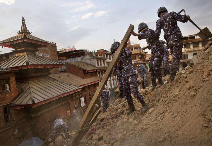 Militares ayudan con las labores de rescate en el lugar donde se levantaba un edificio derrumbado tras el fuerte sismo que sacudió Katmandú, en Nepal.(Foto AP/ Niranjan Shrestha)