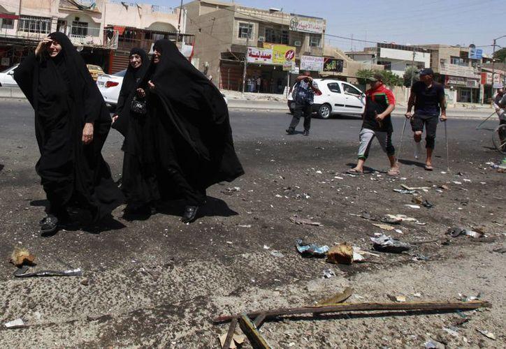 Civiles pasan por el sitio donde estalló una bomba en Bagdad este sábado. (AP Foto/Hadi Mizban)