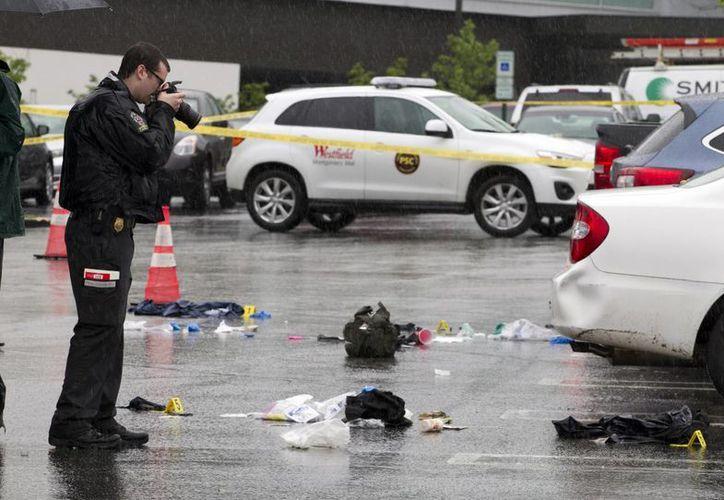 Un agente toma foto de evidencias del tiroteo afuera del Westfield Shopping Center en el suburbio de Bethesda, en el condado de Montgomery. (AP/José Luis Magaña)