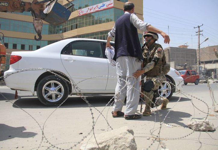 Un agente afgano cachea a un hombre en un control de seguridad en Jalalabad. (Archivo/EFE)