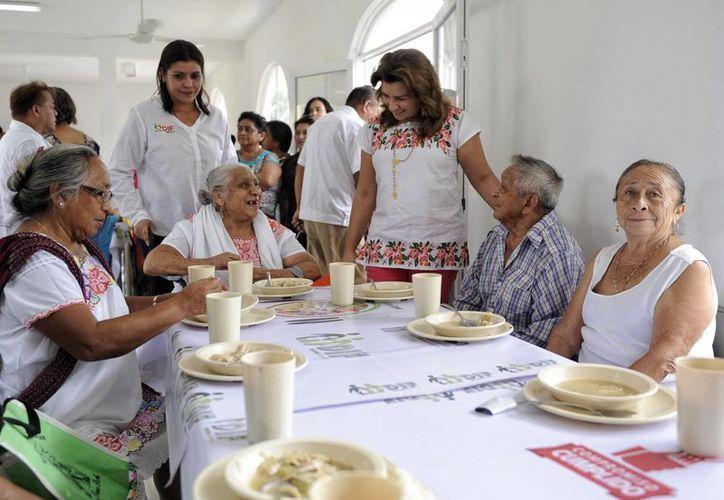 Izamaleños cuentan ya con dos nuevos Espacios de Alimentación Encuentro y Desarrollo, del DIF. En la foto, Sara Blancarte (de pie, la derecha), titular del organismo, convive con beneficiarias. (Foto cortesía del Gobierno de Yucatán)
