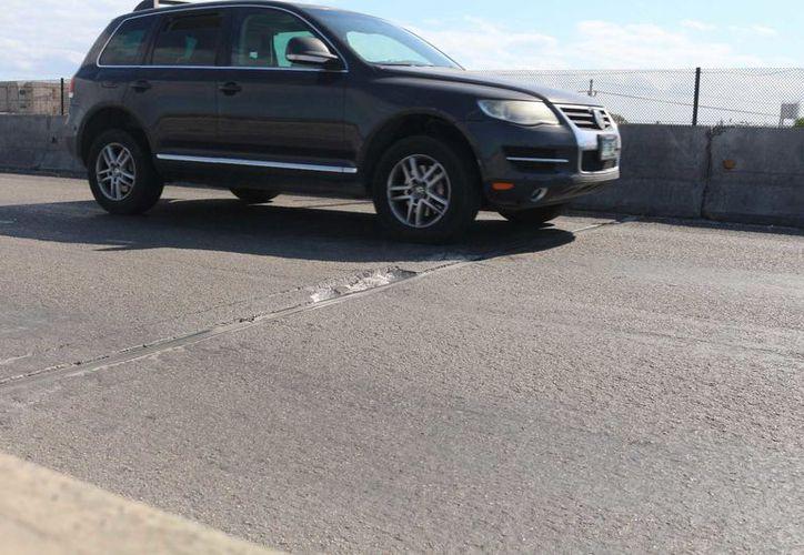 La combinación de encharcamientos y desgaste en la carpeta representa un peligro latente para los automovilistas. (Adrián Barreto/SIPSE)