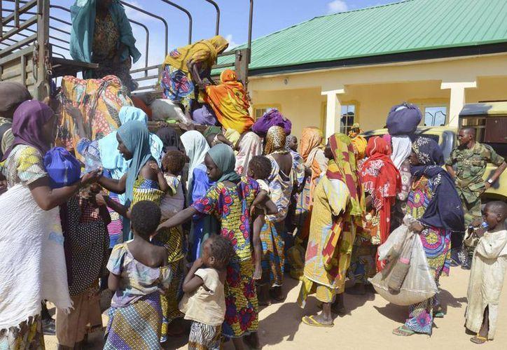 En fotografía, nigerianos llegan a una oficina militar, en Maiduguri. 101 niños, 67 mujeres y 10 hombres fueron liberados del grupo extremista Boko Haram, según información del ejército nigeriano. (AP)