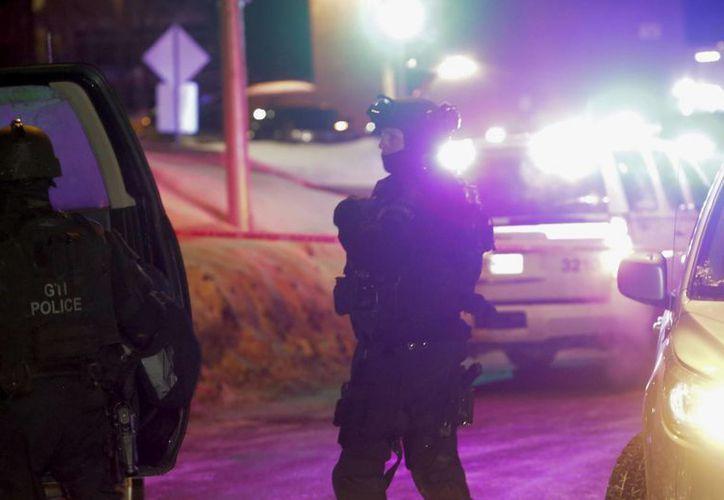 Agentes de policía supervisan las inmediaciones de una mezquita tras una balacera que causó seis muertos, en Quebec. (AP/Francis Vachon)