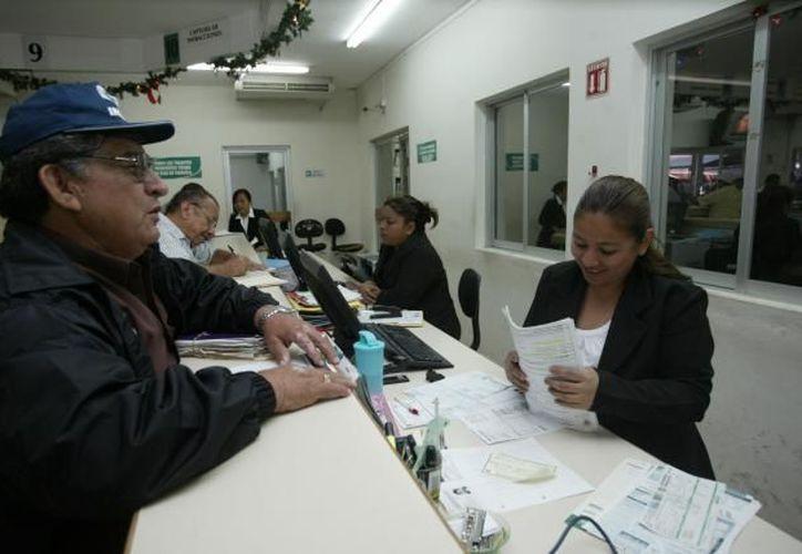 Un automovilista al realizar el trámite del pago de tenencia vehicular. (Archivo/SIPSE)
