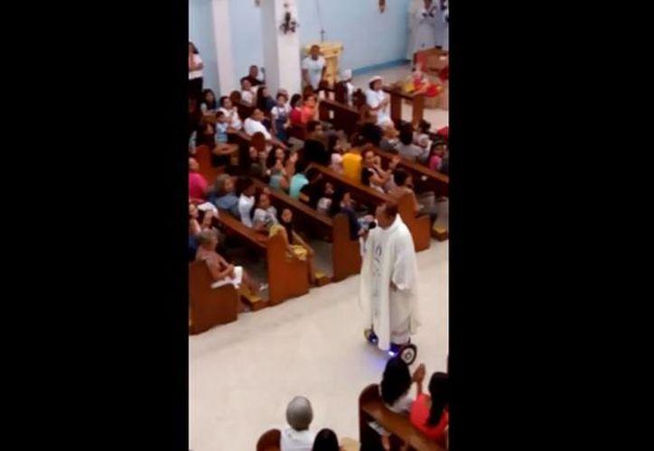 En el video se puede observar cómo el sacerdote canta y se desplaza a bordo de la Hoverboard durante una misa de Nochebuena. (YouTube)