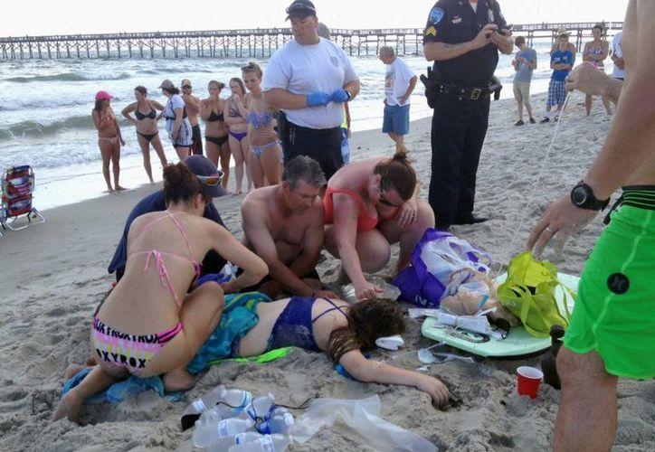 Varias personas prestan primeros auxilios a una joven en el lugar de un ataque de tiburón en Oak Island, Carolina del Norte, el domingo 14 de junio de 2015. (Foto: Steve Bouser/The Pilot, Southern Pines, N.C. via AP)