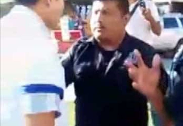 Uno de los policías sujetaba al joven de la camiseta mientras el agraviado le pedía que lo soltará. (Redacción/SIPSE)