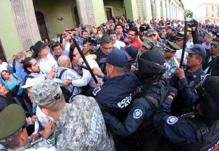 Este jueves, jubilados y pensionadas que realizaban una protesta frente al Palacio de Gobierno de Veracruz, en Xalapa, fueron retirados a la fuerza por elementos de seguridad pública. Los manifestantes exigían el pago de sus aguinaldos y pensiones. (Imagen tomada de jornadaveracruz.com)