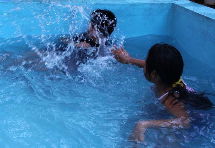 Algunas personas mitigaron el calor con refrescantes baños de piscina. (José Acosta/SIPSE)