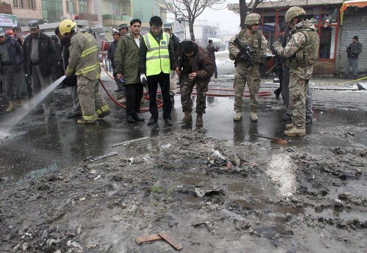Oficiales afganos y soldados estadunidenses inspeccionan la zona de un atentado en Kabul. (EFE/Archivo)
