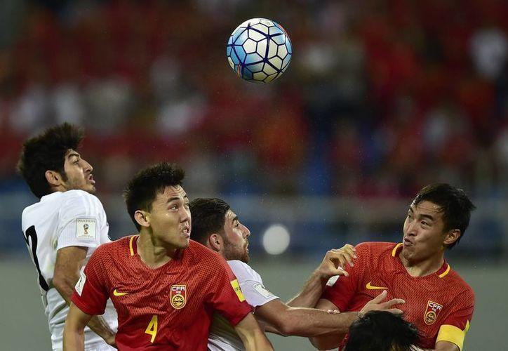 Los chinos son los mejores en muchos deportes, pero solo han acudido a un Mundial de futbol soccer, el de 2002, por lo que ahora han empezado a prepararse para ser potencia mundial en ese rubro. En la foto, partido de eliminatoria entre Irán y China. (AP)