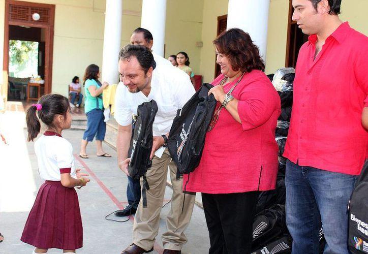 El diputado Francisco Torres Rivas entrega una mochila a una estudiante de la primaria 'Distrito Federal'. (SIPSE)