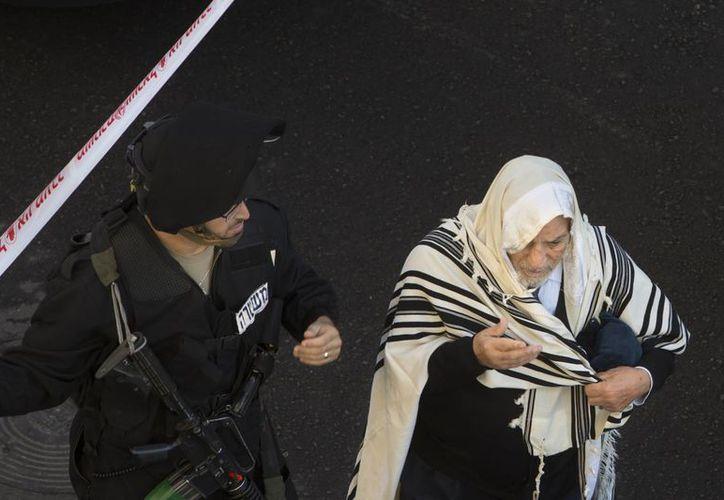 Un oficial israelí acompaña a un hombre ultra-ortodoxo judío cerca de la sinagoga donde ocurrió el homicidio de cuatro personas. (Agencias)