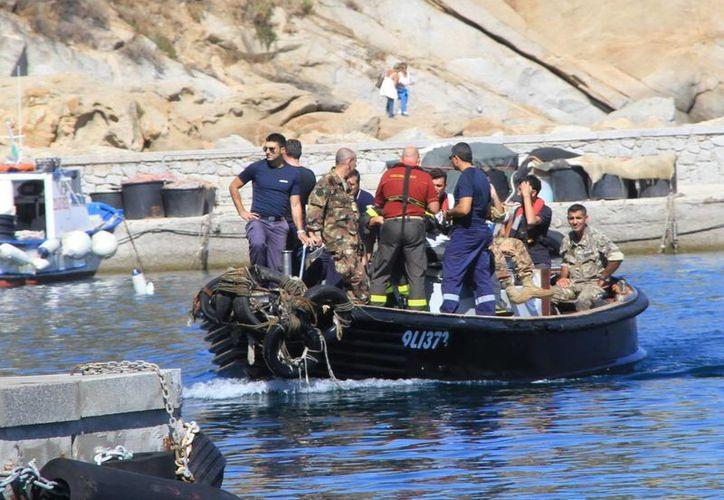 Submarinistas y miembros de una unidad de búsqueda, a bordo de una lancha, participan en las labores de rescate de restos humanos. (EFE)