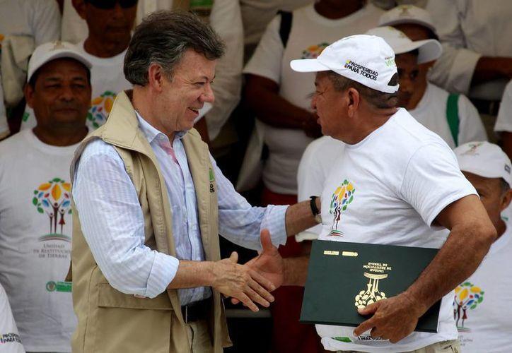 El presidente Santos (i) entrega un título de propiedad en un evento de restitución de tierras en Montería. (EFE)