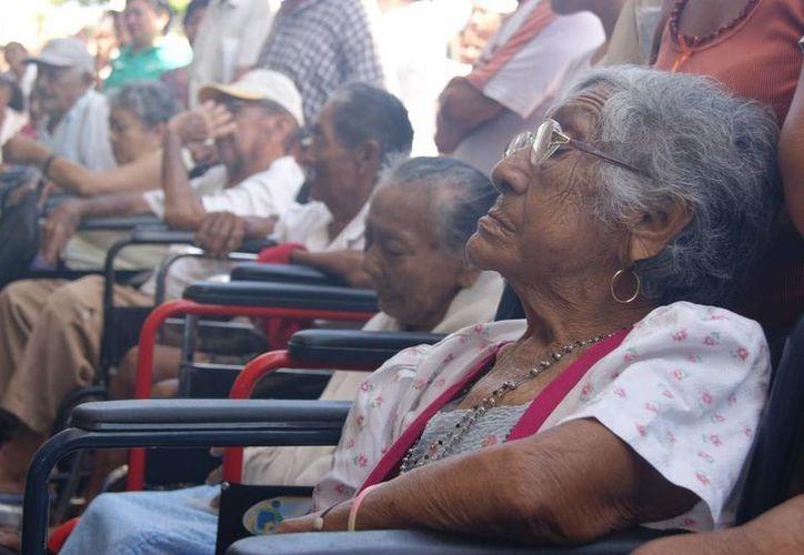 Los ancianos beneficiados en espera de poder cobrar sus apoyos. (Manuel Pool/SIPSE)