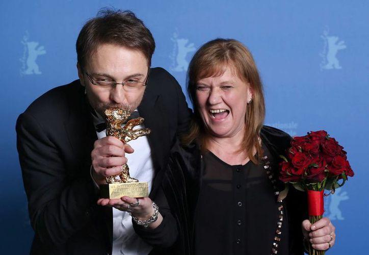 El director rumano Calin Peter Netzer (izq) y la productora Ada Solomon (d) posan con el Oso de Oro a la mejor película para 'Pozitia Copilului'. (EFE)