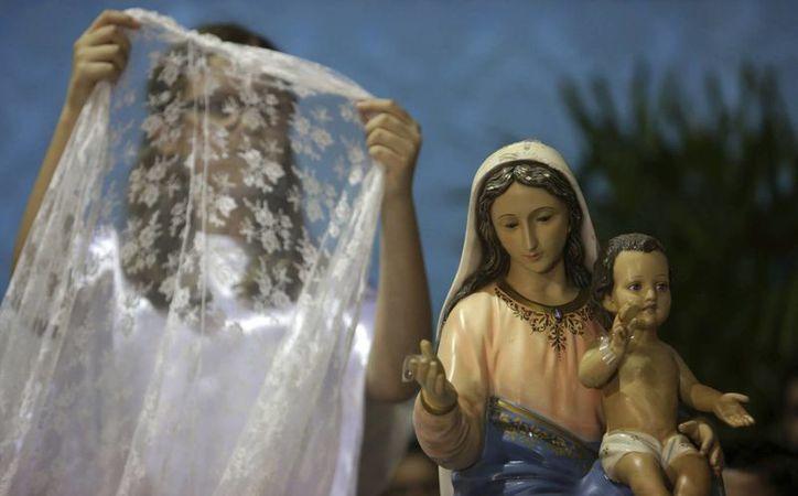 Una niña se prepara a colocar un velo sobre una estatua de Nuestra Señora del Rosario durante la celebración afrocristiana de la Congada en Catalao. (AP/Eraldo Peres)