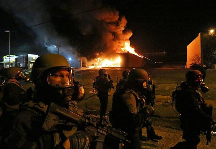 La policía del condado de San Luis arriba a la avenida W. Florissant para dispersar a los manifestantes durante las protestas del lunes por la noche en Delwood, Missouri. (Foto: AP)