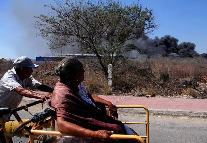 Una pareja cruza por la zona donde se registró el incendio de unas bodegas, en el periférico oriente de Mérida. (José Acosta/SIPSE)
