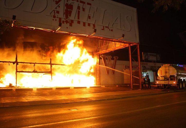 Aunque se detectó a tiempo el inicio del incendio en un baño de Modatelas, no se pudieron controlar las llamas y el fuego se extendió rápidamente. (Martín González/SIPSE)