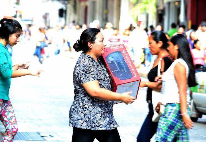 Muchas personas buscan regalos prácticos y útiles. Imagen de una mujer con su compra en el centro de Mérida. (Milenio Novedades)