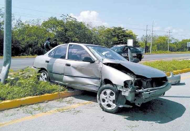 Tras impactarse con el poste y dar un giro, el automóvil quedó atravesado sobre el camellón central de la vía federal. (Redacción/SIPSE)