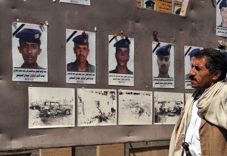 Un hombre en Yemen observa las fotos de los soldados fallecidos en el atentado perpetrado en mayo de 2012 durante los ensayos de un desfile militar. (EFE)