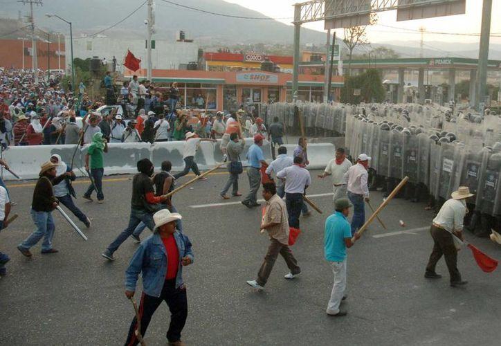 Momento en que profesores de Guerrero se enfrentan a la Policía Federal en la Autopista del Sol. (Notimex)