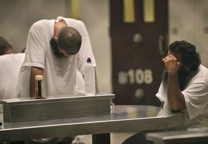 Imagen de archivo, tomada el 31 de mayo de 2009,  muestra a dos detenidos en el centro de detención Camp X-Ray, en la base naval estadounidense de la bahía de Guantánamo, en Cuba. (AP/Brennan Linsley, Pool)