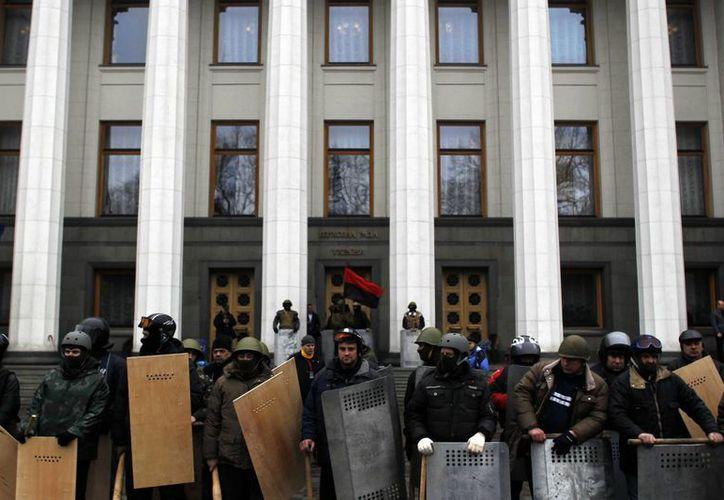 Manifestantes antigubernamentales a las puertas del Parlamento en Kiev. Tras la partida de Yanukovich habrá nuevas elecciones presidenciales. (Agencias)