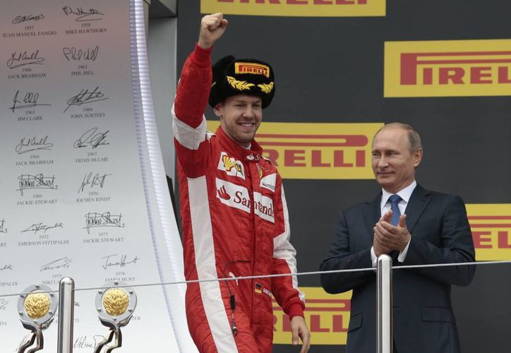 Sebastian Vettel, quien en la foto aparece con el presidente ruso Vladimir Putin el segundo lugar conseguido en el Gran Premio de Sochi, fue sancionado, por lo que se allana el camino de Lewis Hamilton hacia el bicampeonato de F1. (AP)