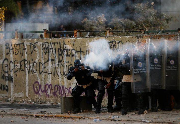 Policías nacionales venezolanos disparan gases lacrimógenos contra los manifestantes durante los enfrentamientos en Caracas, Venezuela. (Agencias)