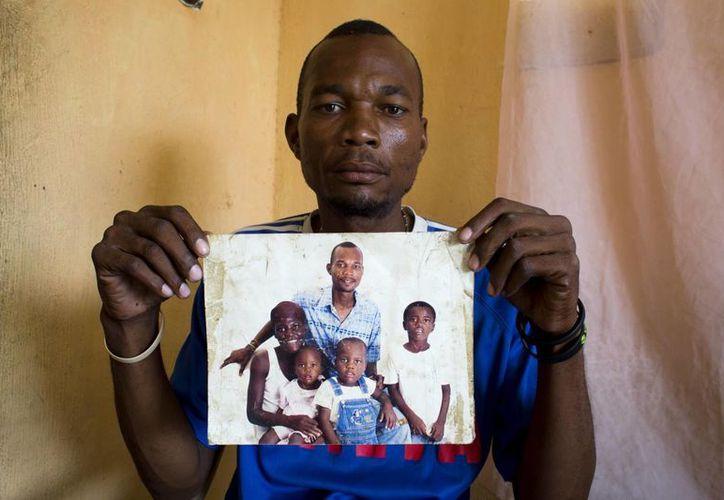 Micheler Castor, que es sordo, sostiene una fotografía en la que aparece con su esposa Jesula Gelin, también sorda, con sus hijos en su casa de Leveque. (Agencias)