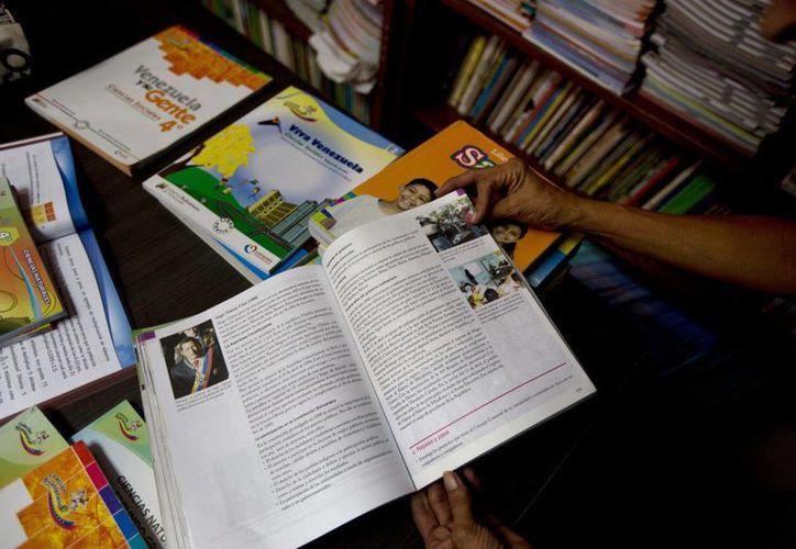 Un profesor muestra una página de un libro de texto con la biografía del difunto presidente venezolano Hugo Chávez en la biblioteca de una escuela pública de Caracas, Venezuela. (Agencias)
