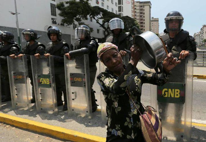Una mujer protesta a cacerolazos frente a policías venezolanos, en Caracas. (Agencias)