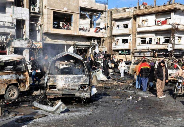 Ciudadanos sirios se congregan en el lugar donde explotaron dos bombas en un puesto de control gestionado por el gobierno, en el vecindario de Zahraa, en la provincia de Homs, en Siria. (Agencias)