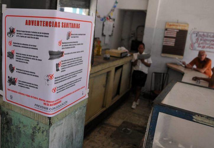 Varias personas conversan en una cafetería, donde se puede ver un cartel alusivo al control sanitario en la capital cubana. (EFE)
