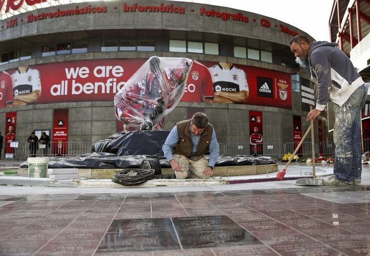 Dos empleados trabajan delante del Estadio de La Luz, de Lisboa, en la construcción de una protección para la estatua del recién fallecido Eusebio da Silva Ferreira. (EFE)