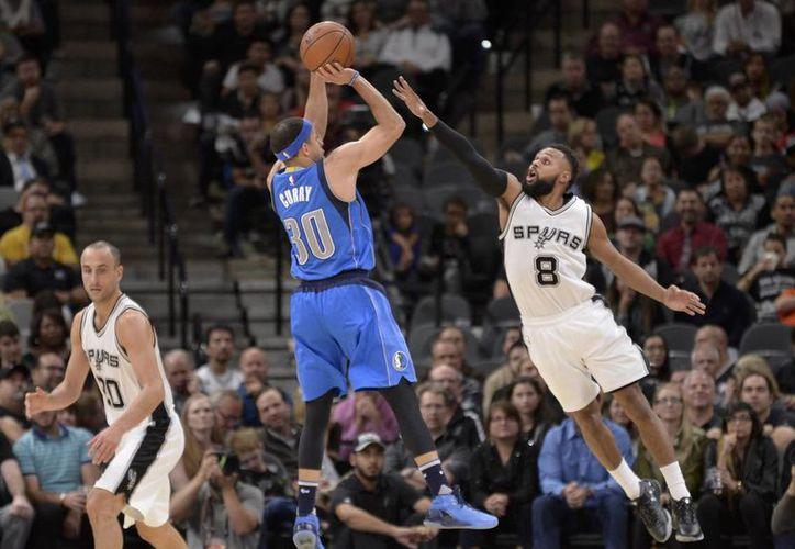 Seth Curry, de Spurs, anota pese a los esfuerzos de Patty Mills, de Mavs, por evitarlo. (AP)