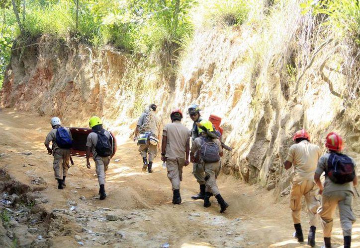 Trabajadores de rescate llegan a la mina de oro, donde un deslizamiento de tierra dejó atrapados a los mineros, en San Juan Arriba, Choluteca en el sur de Honduras. (Agencias)