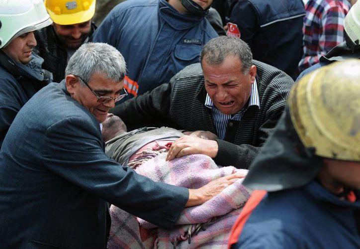 Un hombre llora sobre el cuerpo de un minero, que es sacado por equipos de rescate. (Agencias)