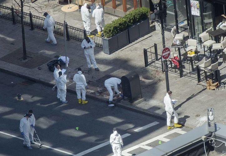 Miembros de la policía recogen pruebas en la avenida Boylston, en Boston. (EFE)